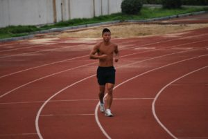 Man Running on a Track for Building Endurance, which is One of The Components of Physical Fitness