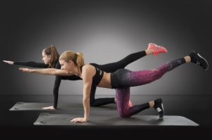 Mother and Daughter Working Out Using a Home Fitness Program